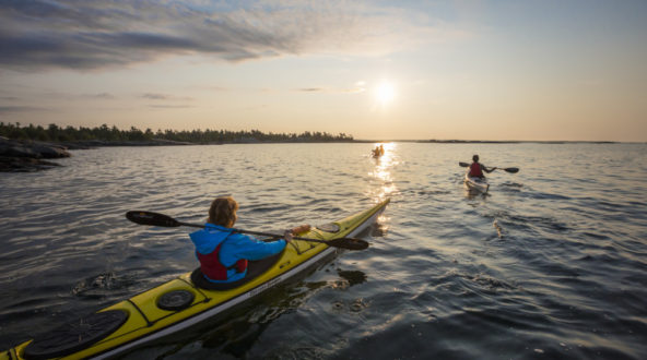 Kayakers paddling into the sunset at White Squall Paddling Centre