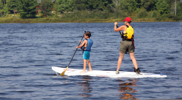Kid and instructor on a SUP board at White Squall Paddling Centre