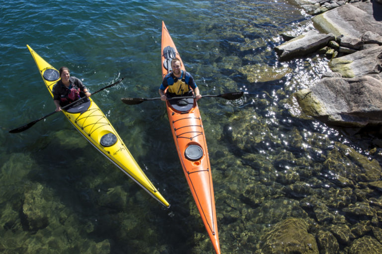 Two students paddling kayaks on a course at White Squall Paddling Centre.